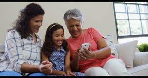 Fille avec la mère et la grand-mère souriant au téléphone portable 4K 4k banque de vidéos