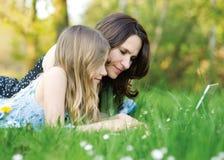 Fille avec la maman sur l'ordinateur Photographie stock libre de droits
