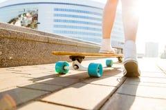 Fille avec la planche à roulettes en bois de longboard Image stock