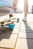 Fille avec la planche à roulettes en bois de longboard Image libre de droits
