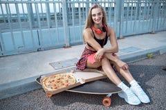 Fille avec la planche ? roulettes et la pizza image stock