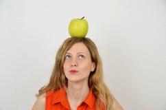 Fille avec la pomme verte d'isolement sur le blanc Photographie stock