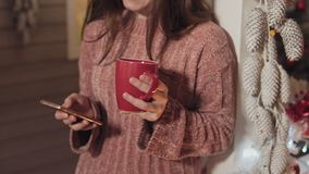 Fille avec la position de téléphone au porche avec l'arbre de Noël et aux lumières au fond clips vidéos