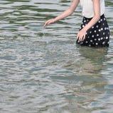 Fille avec la robe pointillée éclaboussant l'eau Images stock