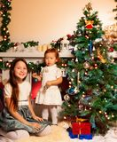 Fille avec la soeur décorant l'arbre de Noël Images libres de droits
