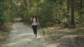 Fille avec la tasse du café et du chien appréciant une promenade chez la belle personne de forestFemale et du chien mixbreed alla clips vidéos