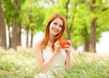 Fille avec la tasse orange Image stock