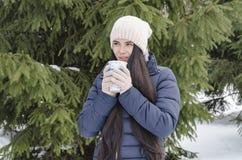 Fille avec la tasse thermo, après-midi givré d'hiver image libre de droits
