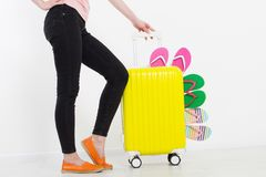 Fille avec la valise d'isolement sur le fond blanc Vacances d'été bascules électroniques ou pantoufles d'été Mallette ou sac de v photographie stock
