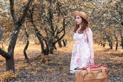 Fille avec la valise en cuir pour le voyage en parc d'automne sur la promenade photos stock