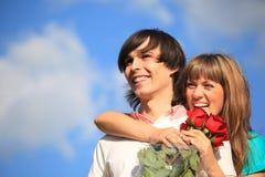 Fille avec le bouquet des étreintes de roses derrière le type Photographie stock libre de droits