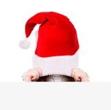 Fille avec le chapeau rouge de Santa jetant un coup d'oeil derrière un conseil vide O d'isolement photographie stock