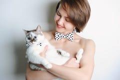 Fille avec le chat aux yeux bleus Dans le même point de polka de noeuds papillon Sans habillement Double-regard à la mode Fond bl Photo libre de droits