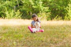 Fille avec le chat blanc se reposant sur l'herbe dehors photographie stock