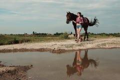 Fille avec le cheval brun Photographie stock libre de droits