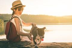 Fille avec le chien se reposant par un lac Photo libre de droits