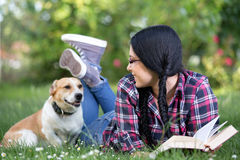 Fille avec le chien sur l'herbe Photos libres de droits