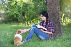 Fille avec le chien sur l'herbe, lisant un livre Photos libres de droits