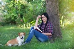 Fille avec le chien sur l'herbe, lisant un livre Image stock