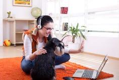 Fille avec le chien utilisant le faire appel visuel à l'ordinateur portable Image stock