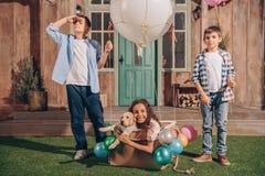 Fille avec le chiot de Labrador se reposant dans la boîte de ballon à air avec des amis se tenant tout près Image libre de droits