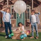 Fille avec le chiot de Labrador se reposant dans la boîte de ballon à air tandis que garçons regardant loin Image libre de droits