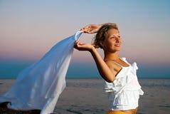Fille avec le foulard sur le coucher du soleil Photographie stock libre de droits
