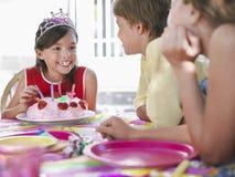 Fille avec le gâteau parlant aux invités à la fête d'anniversaire Photographie stock libre de droits