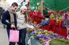 Fille avec le garçon choisissant la fleur de Noël Photo libre de droits