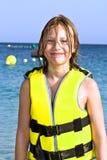 Fille avec le gilet de vie à la plage Photographie stock libre de droits