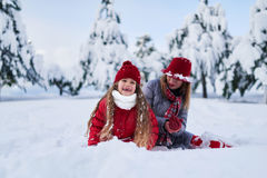 Fille avec le jeu de mère en parc couvert de neige Photo stock