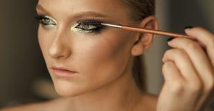 Fille avec le jeune visage dans le salon de beauté Brosse d'applicateur de mascara d'utilisation de femme, maquillage Peau modèle photos libres de droits