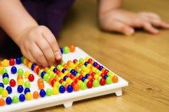 Fille avec le jouet éducatif de puzzle de goupille Image libre de droits