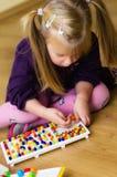 Fille avec le jouet éducatif de puzzle de goupille Photographie stock libre de droits