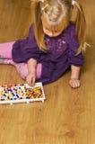 Fille avec le jouet éducatif de puzzle de goupille Photos stock