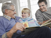 Fille avec le livre d'histoire d'And Grandfather Reading de père Photographie stock
