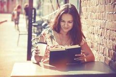 Fille avec le livre de lecture de café Photographie stock