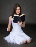 Fille avec le livre et une baguette magique magique Image stock