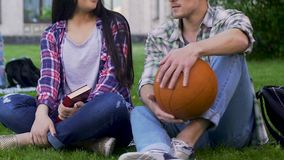 Fille avec le livre, type avec l'herbe se reposante et parler de boule de basket-ball, relations clips vidéos