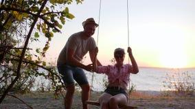Fille avec le mâle sur la mer de côte d'ot de bascule dans le crépuscule, reste d'été des amants sur le remblai dans le coucher d clips vidéos
