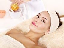 Fille avec le masque de massage facial d'or. Image libre de droits