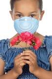 Fille avec le masque et la fleur Photographie stock libre de droits