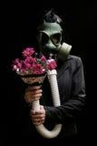 Fille avec le masque et les fleurs de gaz Photographie stock libre de droits