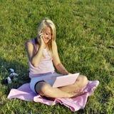 Fille avec le netbook et le téléphone roses photographie stock libre de droits
