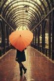 Fille avec le parapluie marchant à l'allée dans le jour pluvieux Image libre de droits