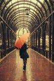 Fille avec le parapluie marchant à l'allée dans le jour pluvieux Images libres de droits