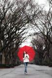 Fille avec le parapluie rouge marchant en parc dans la chute Photos libres de droits