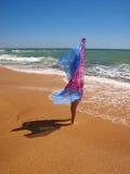 Fille avec le pareo restant sur une plage ensoleillée photo stock