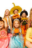 Fille avec le potiron, amis dans le costume de Halloween Image libre de droits