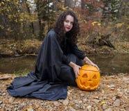 Fille avec le potiron par la rivière Photographie stock libre de droits